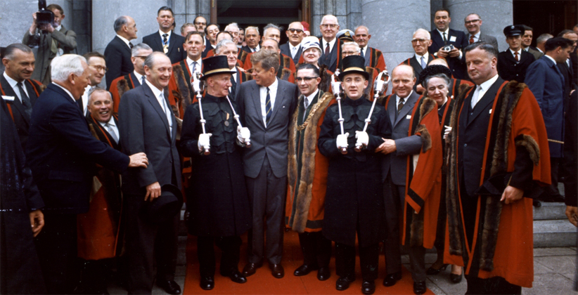 JFK, relaxed and smiling, outside City Hall with Lord Mayor Sean Casey, members of the Cork Corporation, and mace bearers. (Robert Knudsen, JFK Presidential Library)