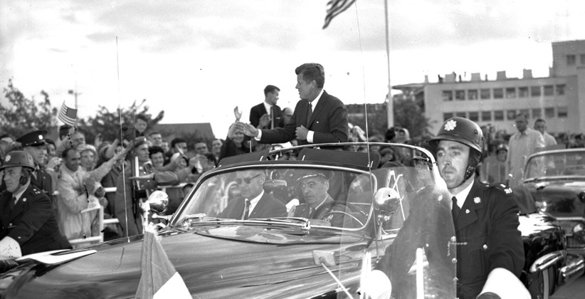 JFK standing in the open-topped car so vivdly recalled by many who saw him. (NLI, Independent Newspapers Collection)