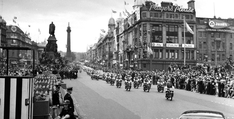The long motorcade travels down a packed O'Connell Street towards O'Connell Bridge. (NLI, Independent Newspapers Collection)