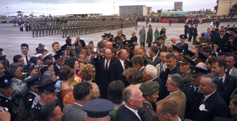 Police and photographers surround JFK at Shannon, as he meets the Bunratty Castle Singers.