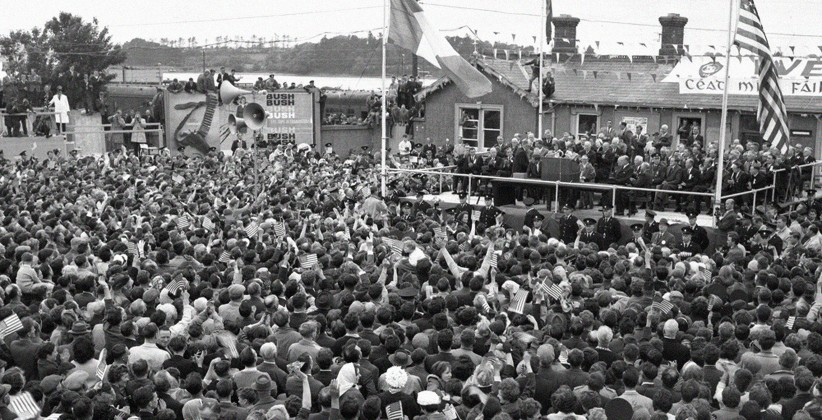 A large crowd surround podium. A few people sit on roof behind podium too. Flags flying, 'Céad Míle Fáilte' banner. (JFK Presidential Library)